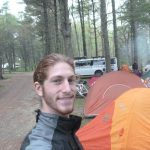 Michael Altfield takes a selfie by his tent at a forest campground