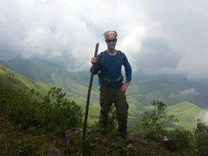 Michael Altfield holding a bamboo trekking pole, surrounded by clouds and lush green, rolling hills