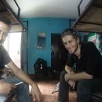 Michael Altfield sits on a bunk bed at a hostel smiling with a Nuri Funas opposite